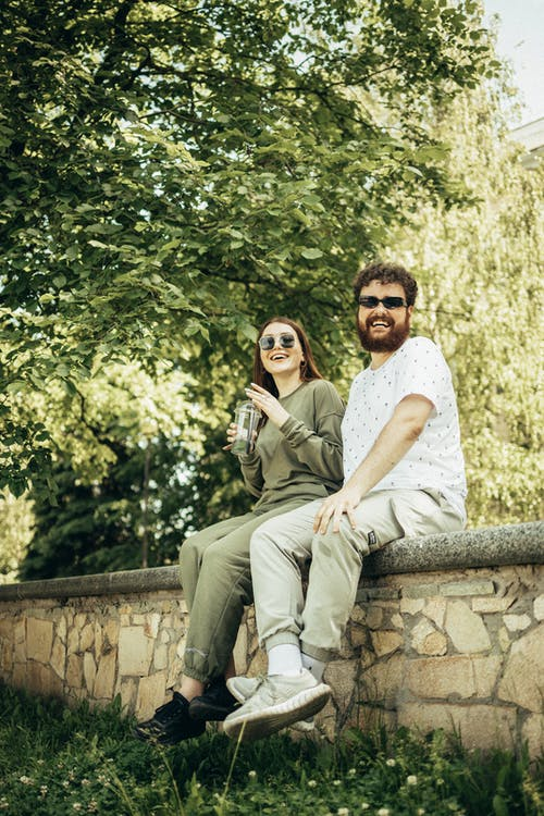 Man and Woman Sitting on Concrete Bench
