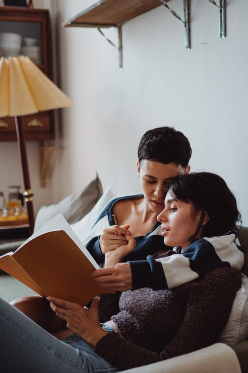 Two Women Cuddling and Reading a Book
