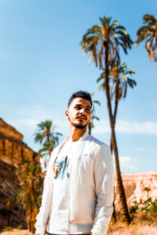 Man in White Long Sleeve Shirt Standing Near Palm Tree