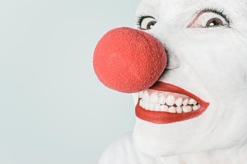Smiling Person With Pink Lipstick and Red Nose Clown