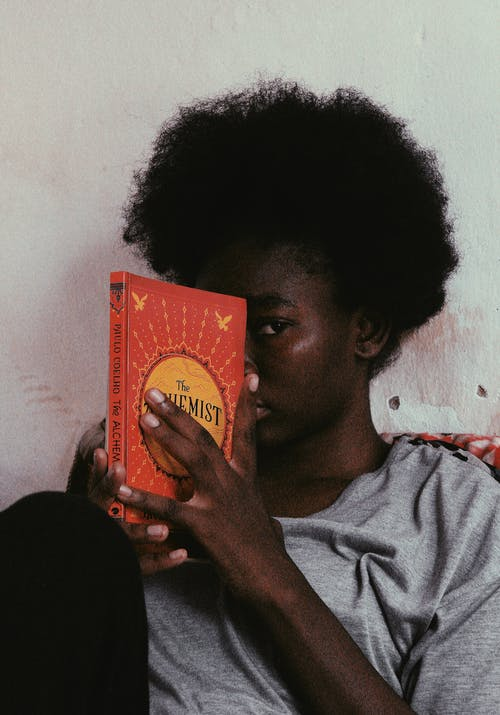 Black female covering face with book