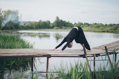 Woman in Black Long Sleeve Shirt and Black Pants Sitting on Brown Wooden Dock over River