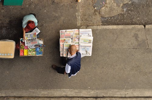 Man in Blue Jacket and Green Hat Reading Newspaper