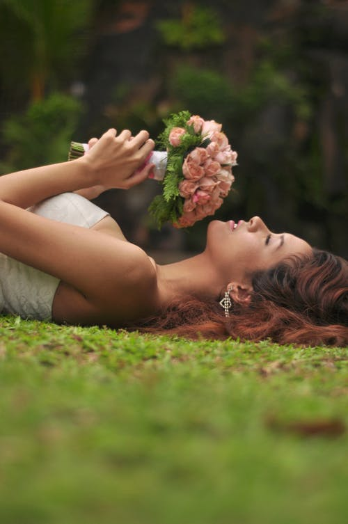 Woman in White Dress Lying on Green Grass Field Holding Bouquet of Flowers