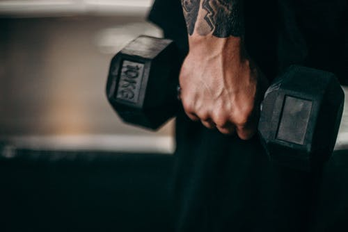 Person Holding Black Dumbbell With Black Tattoo