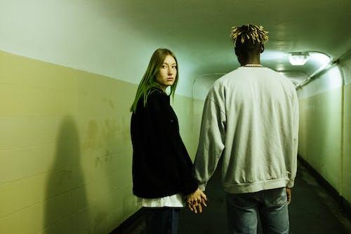 Man in Gray Sweater Standing Beside Woman in Black Jacket