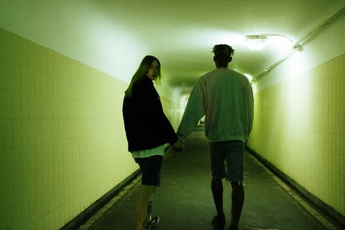 Man and Woman Walking on Hallway