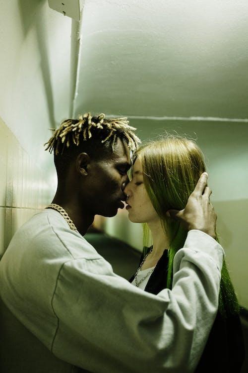 Man and Woman Kissing Near Green Wall