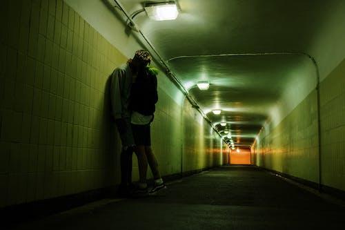 Man in Black Jacket and Black Shorts Walking on Hallway
