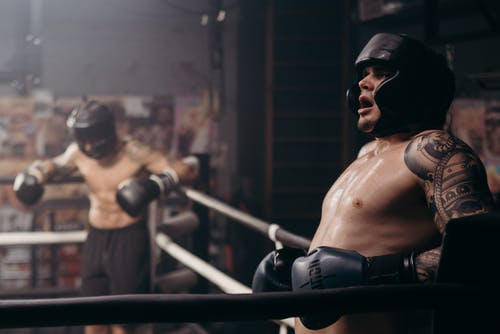 Topless Man Wearing Black Sunglasses and Black Boxing Gloves
