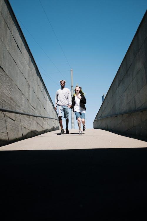 2 Women Walking on Brown Sand Near Gray Concrete Building