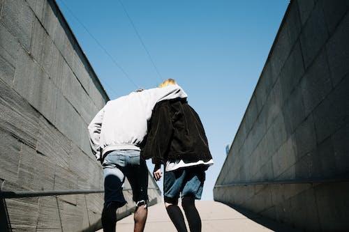 Man in White Shirt and Black Jacket Walking on Street