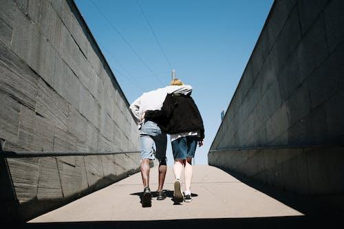 Mujer En Chaqueta Negra Y Pantalones Cortos De Mezclilla Azul Caminando Por La Acera