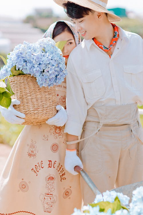 Delighted couple of Asian farmers wearing headdresses standing on farmland with blue flowers on summer day in countryside in sunny weather