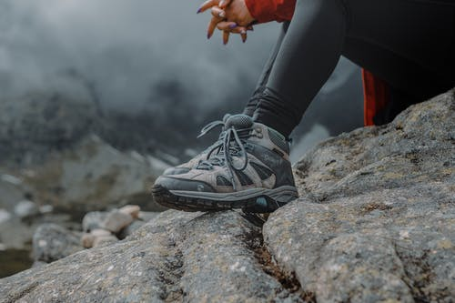 Person Wearing Hiking Shoes Sitting on a Rock