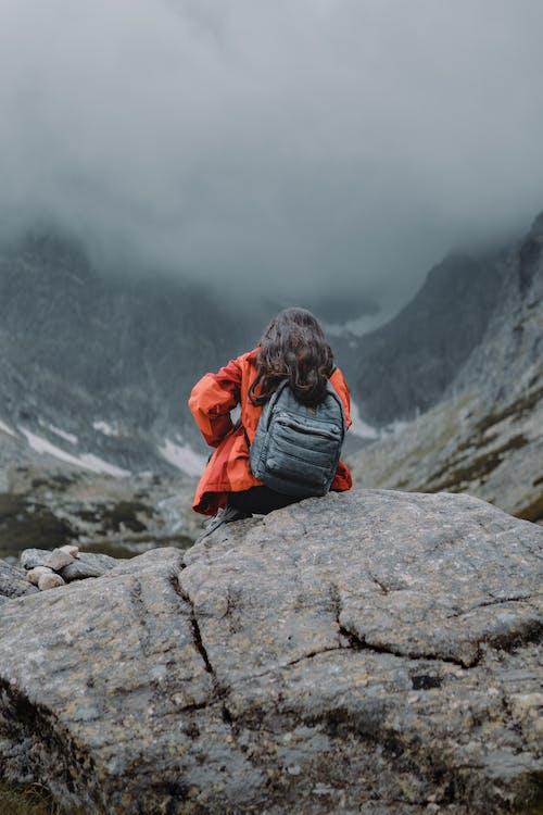 Person in Orange Jacket Sitting on a Rock