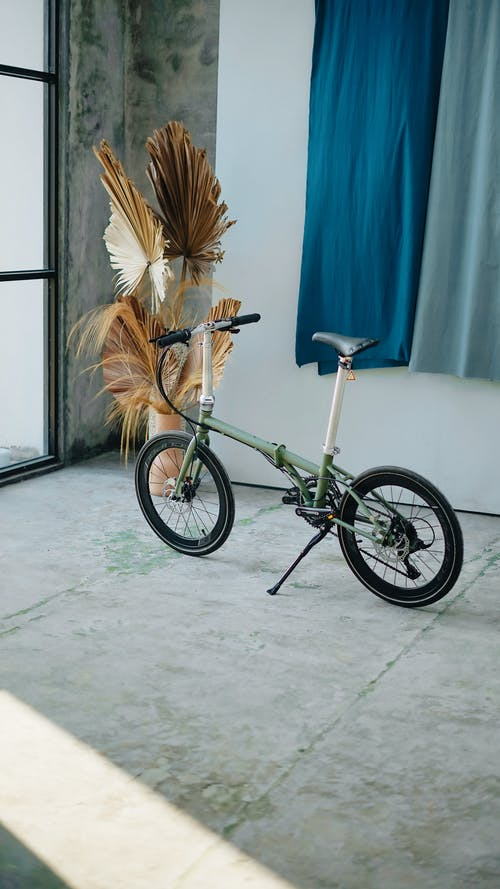 Small green bicycle parked on floor in sunny room with dried plant in vase and colorful fabric hanging on wall