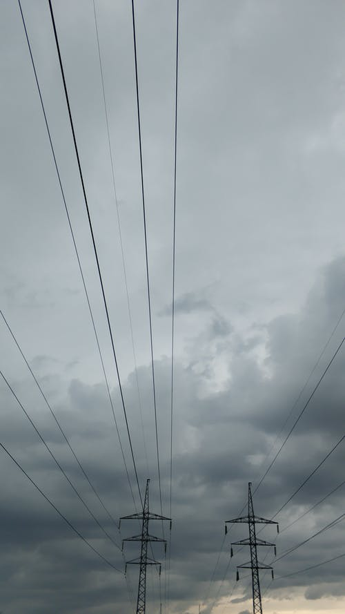 From below power line with poles and wires against gray cloudy sky at dusk