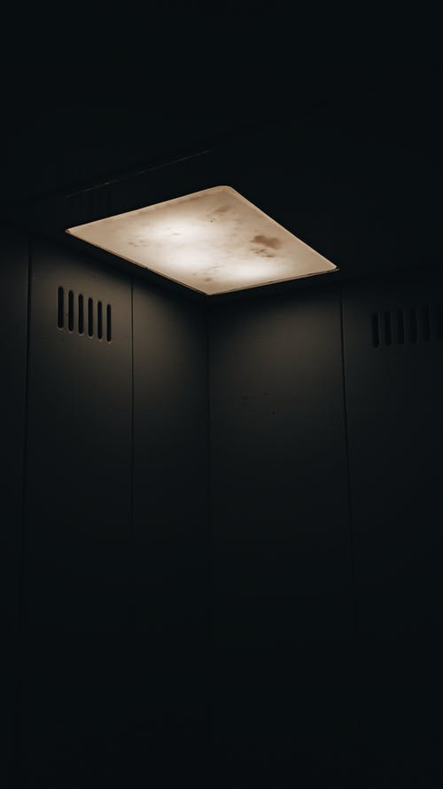 Dim lamp with stains shining in dark elevator