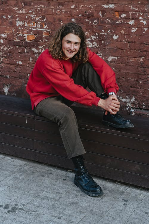 Woman in Red Hoodie and Black Pants Sitting on Brown Concrete Bench