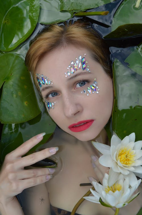 Serious woman with rhinestones lying in water