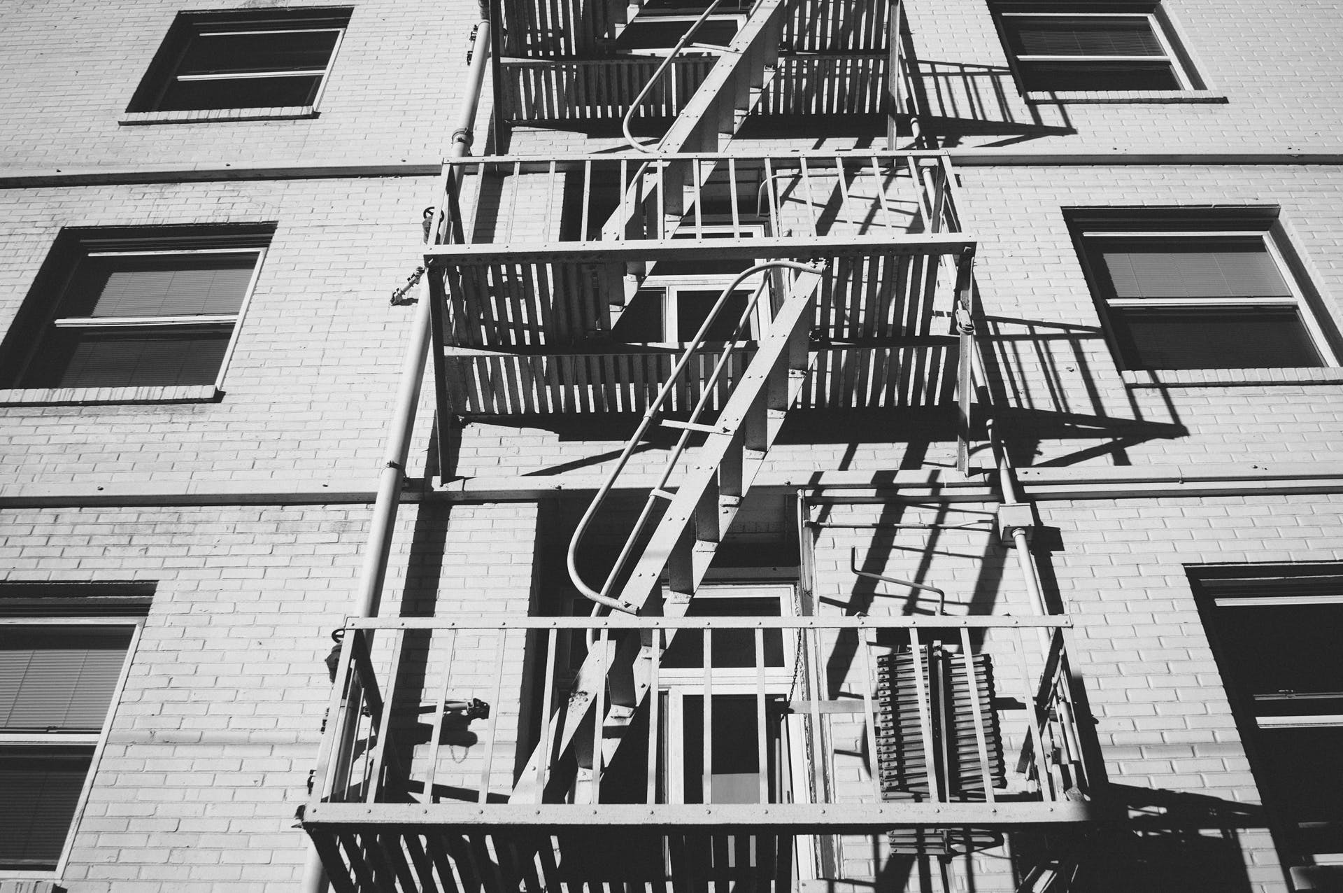 Grayscale Photo of Escape Stairs