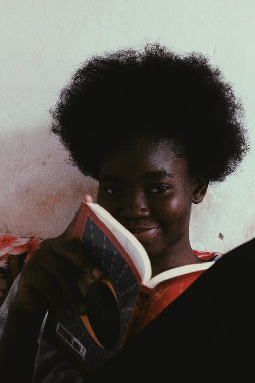 Cheerful black woman holding book