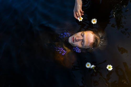 Person swimming in water with flowers