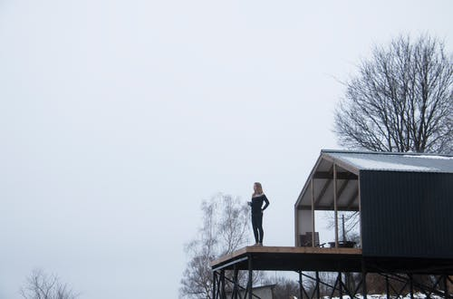 Man in Black Jacket Standing on Brown Wooden Roof