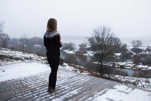 Woman in Black and White Striped Long Sleeve Shirt and Black Pants Standing on Snow Covered