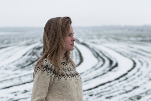 Woman in Brown Knit Sweater Standing on Snow Covered Ground