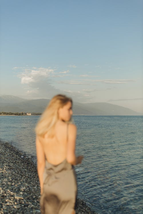 Topless Woman Standing on Rocky Shore