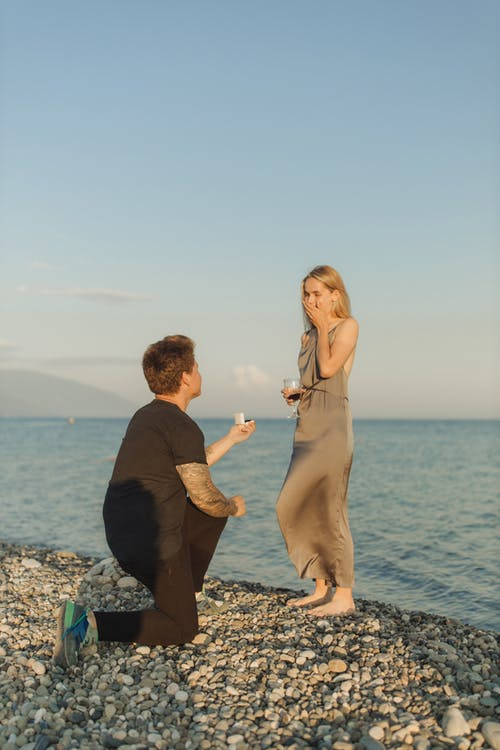 Man in Black Long Sleeve Shirt Holding Woman in Brown Dress on Beach