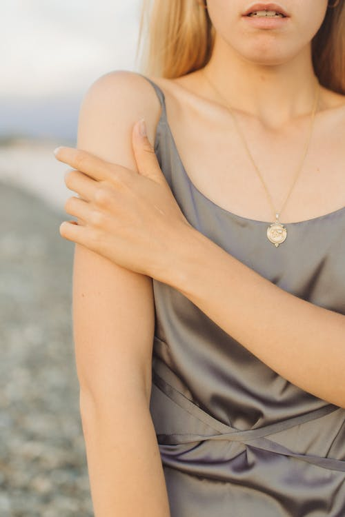 Woman in Black Sleeveless Dress Wearing Silver Necklace