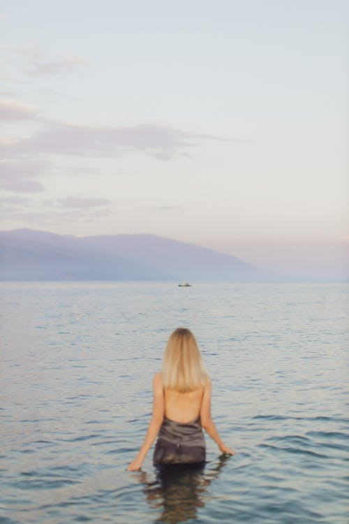 Woman in Brown Tank Top Standing on Sea Shore