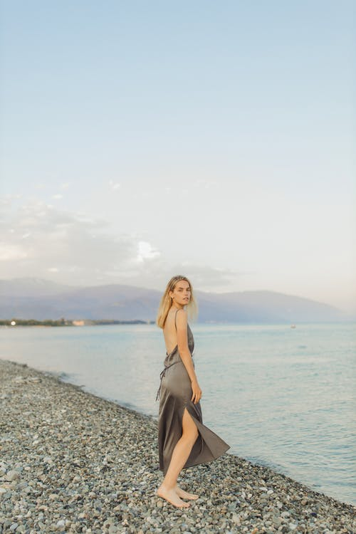 Woman in Black Spaghetti Strap Dress Standing on Gray Sand Near Body of Water