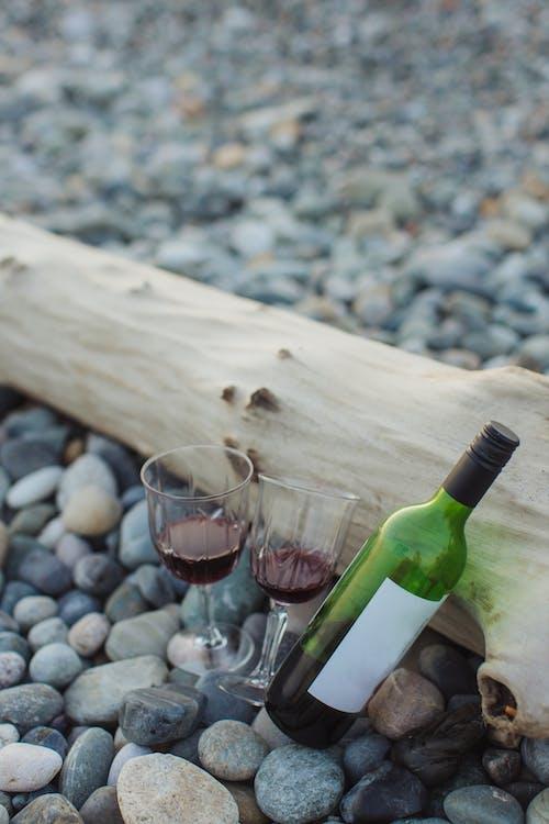 Wine Bottle Beside Wine Glass on Brown Wooden Table
