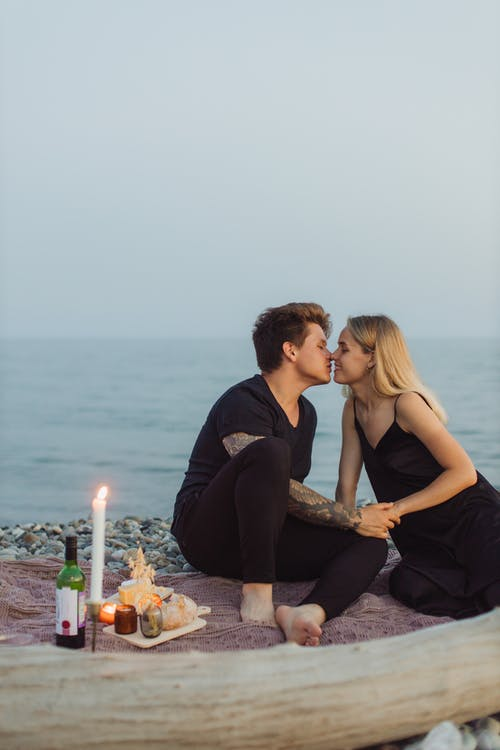 Couple Sitting on Rock Near Body of Water during Sunset