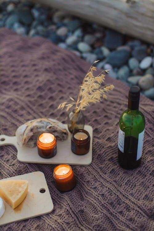 Green Glass Bottle Beside White Ceramic Mug on Brown Wooden Table