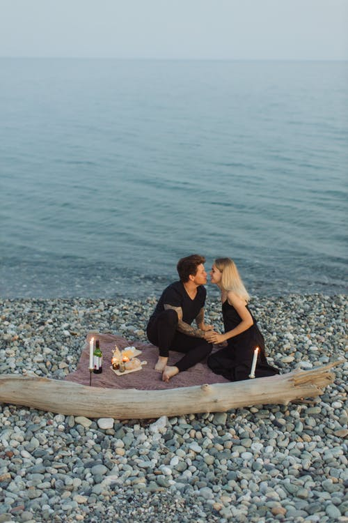 Man and Woman Sitting on Brown Wooden Boat on Sea Shore