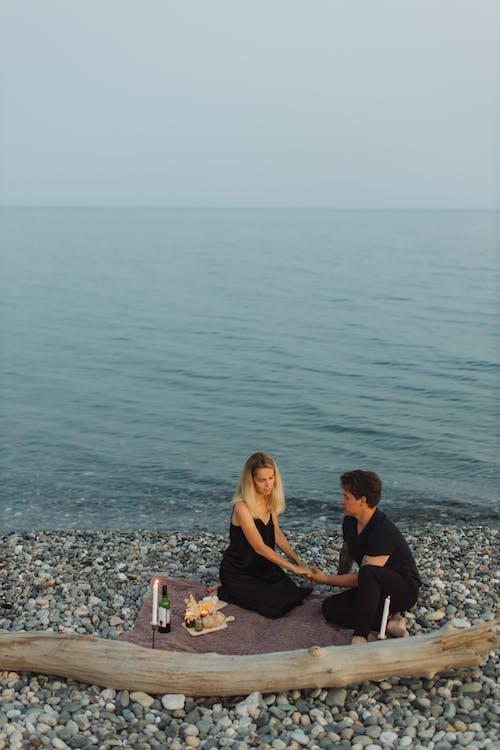 2 Women Sitting on Rocky Shore
