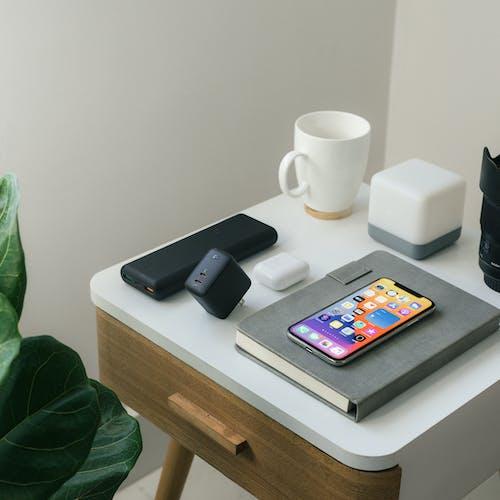 Iphone 4 Noir à Côté De La Tasse En Céramique Blanche Sur Table En Bois Blanc
