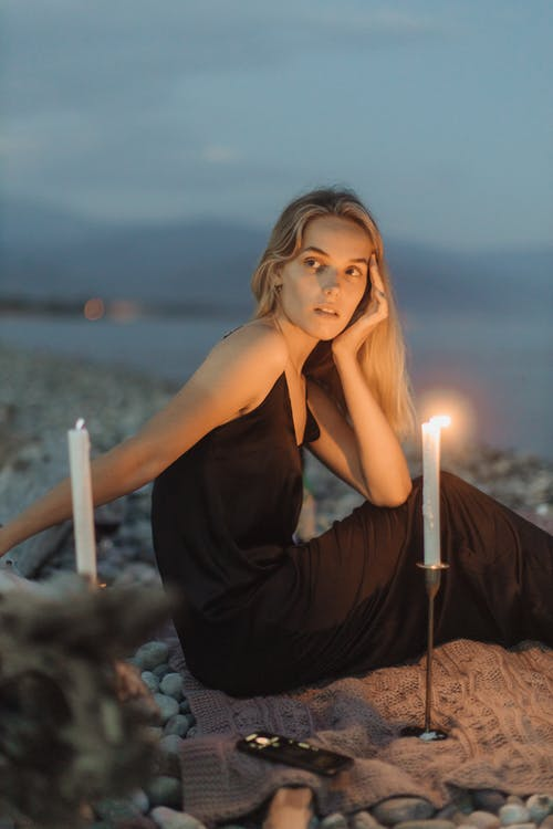 Woman in Black Spaghetti Strap Dress with Candles