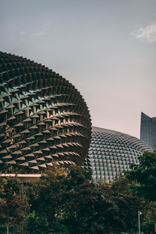 Facade of eye catching geometric Esplanade building with spiked domes located in park in Singapore under blue sky