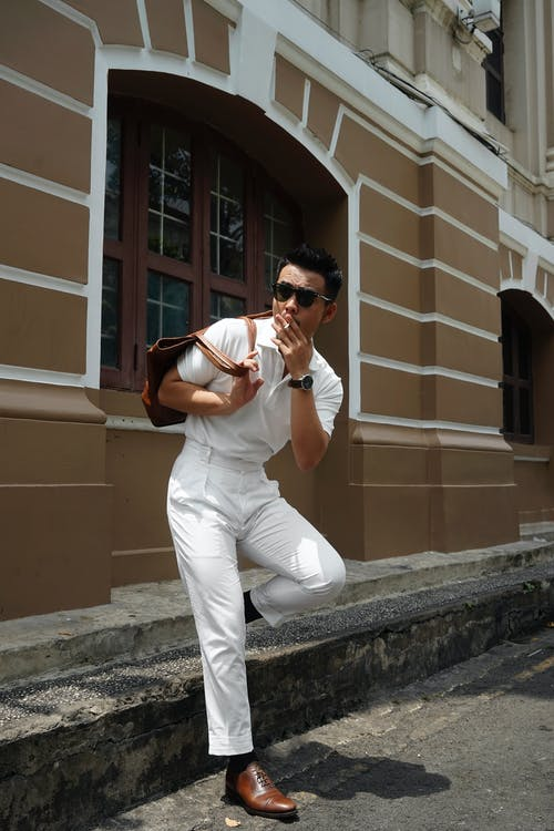 Man in White T-shirt and White Pants Sitting on Concrete Bench