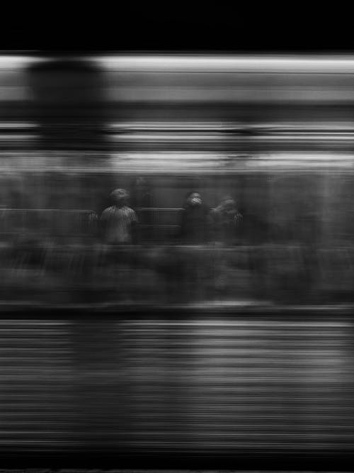 Black and white shot of unrecognizable person standing near window in subway car while riding