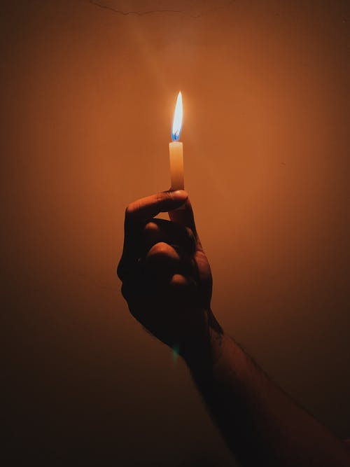Hand with burning candle in darkness