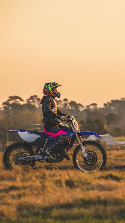 Man in Black Jacket Riding Blue and Black Motocross Dirt Bike