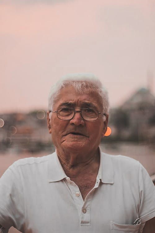 Close-Up Shot of an Elderly Man in White Polo Shirt and with Eyeglasses