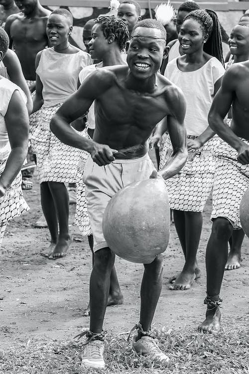 Black and white African man playing authentic rhythmic instrument while having fun at traditional event